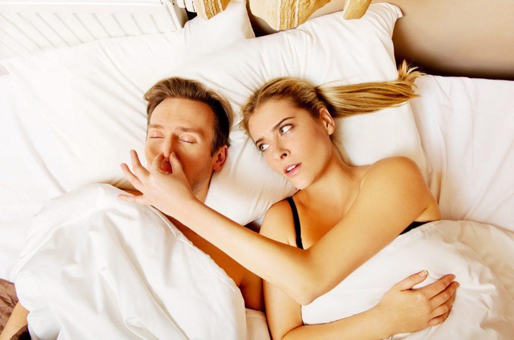 Мъж в легло, който хърка.